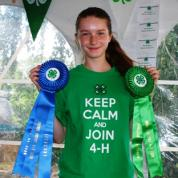 A female 4-H student holds a blue and a green contest ribbon